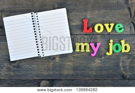 Love my job and notepad word on wooden table