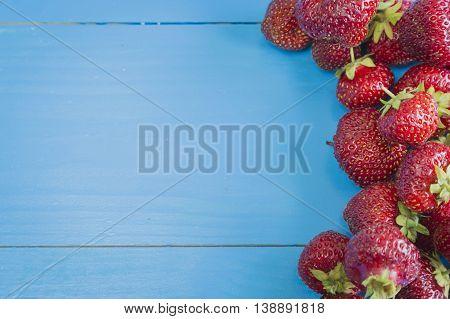 Fresh strawberries on blue wooden background, copyspase