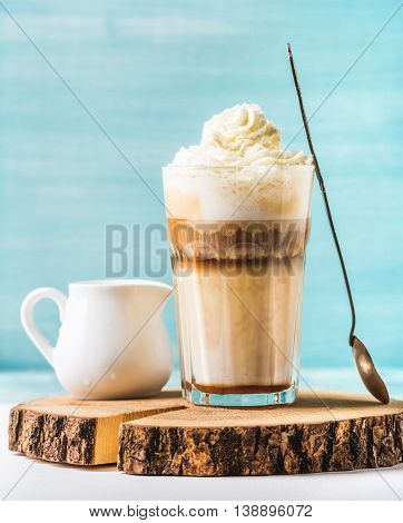 Latte macchiato with whipped cream, serving silver spoon and white pitcher on wooden round board over blue painted wall background, selective focus, vertical composition