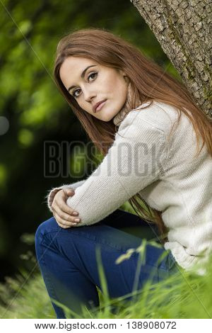 Outdoor portrait of beautiful thoughtful sad girl or young woman with red hair wearing a white jumper sitting & leaning against a tree in the countryside