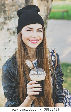 Cool teenage girl drinking coffee outdoors. Beautiful cheerful young woman in black leather jacket and black beanie hat drinking takeaway beverage in park. Closeup, matte filter applied.