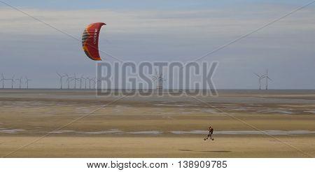 WALLASEY, ENGLAND, JULY 3. A tidal flat on July 3, 2016, near Wallasey, England. A man skateboards across the tidal flat sand using a parasail near Wallasey England.
