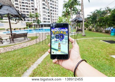 California, United States, July 2016 : Hand holding a cellphone to play Pokemon Go with blur garden background