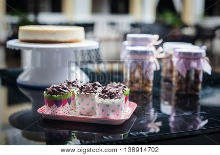 Cheese cake and cookies inside jar on top of table