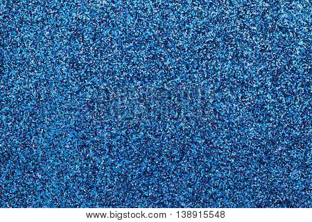 Sparkling background of dark blue small sparkles closeup. Brilliant backdrop.