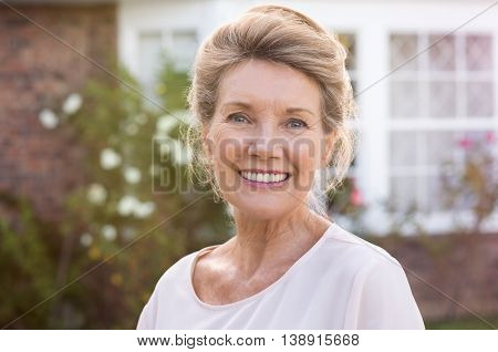 Happy senior woman standing outside her house. Content woman smiling and looking at camera. Portrait of cheerful old grandmother relaxing outside the house.