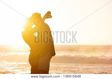 Young loving couple embracing on the beach at sunset. Romantic couple hugging and looking each other on the beach against ocean during sunset. Young attractive couple in love.