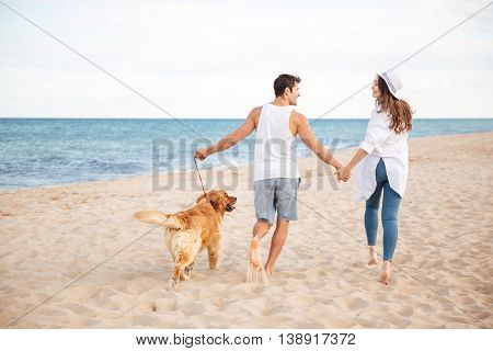 Back view of happy joyful young couple running on the beach with their dog