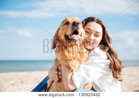 Closeup of tender smiling young woman hugging her dog on the beach