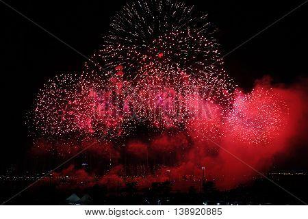 Red fireworks on sky. International Fireworks. Fireworks display on dark sky background.