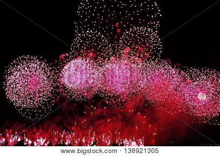 Pink fireworks on sky. International Fireworks. Fireworks display on dark sky background