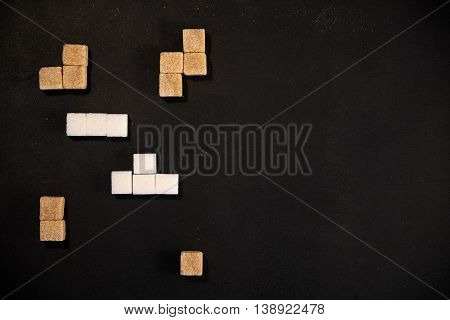Brown and white sugar cubes arranged in tetris shapes with copy space on the right