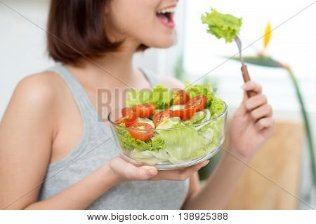 close-up of woman eating fresh salad. Dieting concept. Healthy Food.
