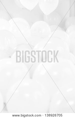 A sea of white balloons in a stark white room