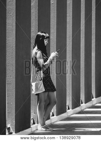 young woman addicted to mobile phone in monochrome