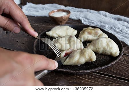 dumplings with cherries on a brown plate dumplings on a brown background fork and knife in hand cutting dumplings dumplings with cherries on a wooden table