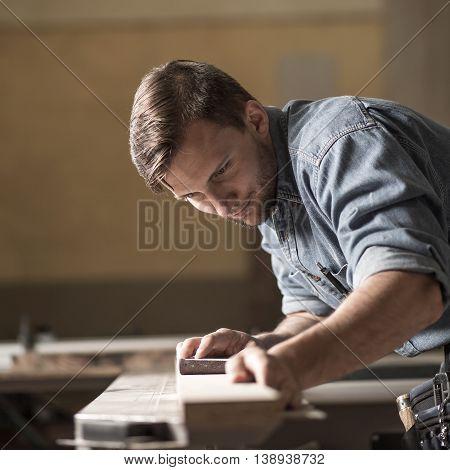 Carpenter Sanding Wooden Plank