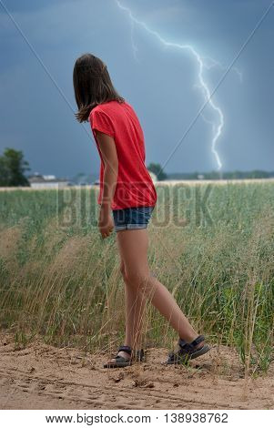 Girl teenager watching the lightning discharge in the field.