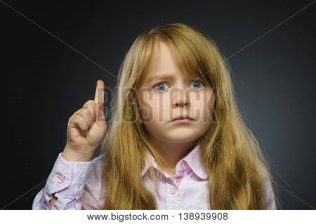 Portrait of displeased angry girl with threatens finger isolated on gray background. Closeup.
