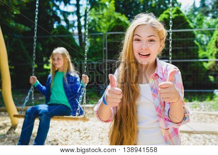 Portrait of happy and smiling child show thumb up at park. On the background other girl riding a swing.