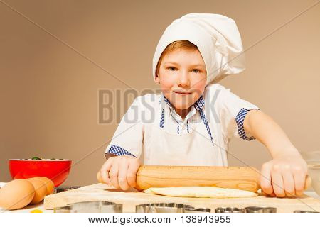 Close-up portrait of boy in baker's uniform, flattening dough with wooden rolling pin for cookies, background with copy-space