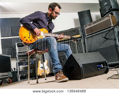 Photo of a man in his late 20's sitting in a recording studio playing his electric guitar.