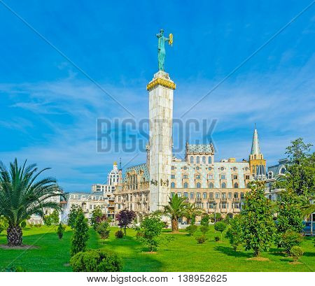 The bronze statue of Medea with the golden fleece rises over the mansions and greenery of Europe Square Batumi Georgia.