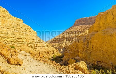 The walk along the scenic orange canyon in Ein Gedi Nature Reserve Judean desert Israel.