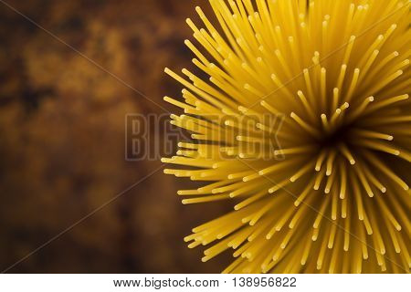 Yellow long spaghetti on a rustic background. Yellow italian pasta. Long spaghetti. Raw spaghetti bolognese. Raw spaghetti Food background concept.