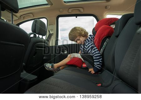 Little boy faste seat belt in high back booster car seat. Child safety.