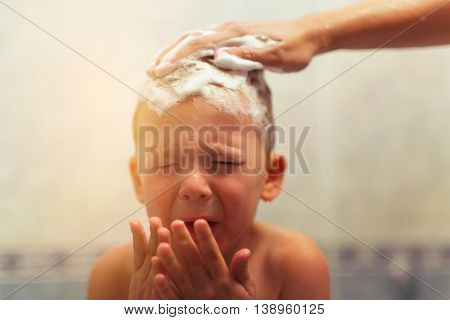Boy taking a bath and crying. Little boy upset in a bathtub mother's hand washing his hair with shampoo and soap