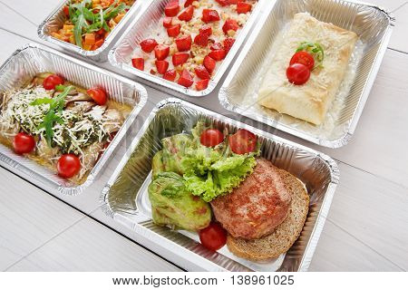 Healthy food background. Take away of natural organic food in foil boxes. Fitness nutrition, meat, vegetable and berry cereal. Top view, flat lay.