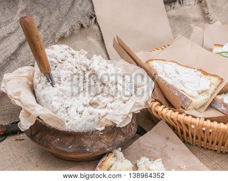 People put pate on hearth bread from pot. Open air