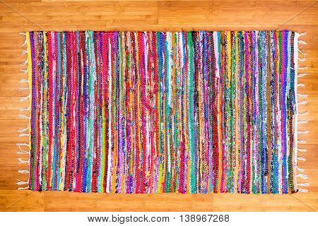 Close up on hand woven rug with red blue yellow purple and other colors over bamboo floor as frame