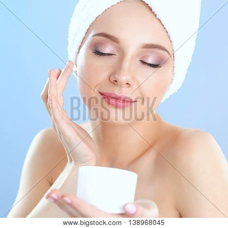 Beautiful young woman applying a creme on her face isolated on gray background.
