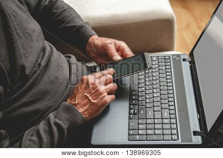 Senior sitting on a sofa with mobile phone in hand and laptop. Working in retirement concept
