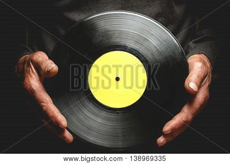 Vintage vinyl record in the hands of an elderly man.