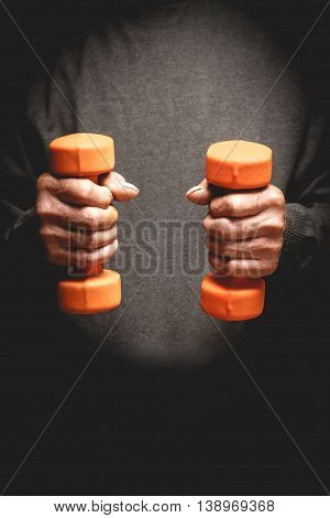 Orange dumbbells in the hands of an elderly man. Sports retired. Photo in low key