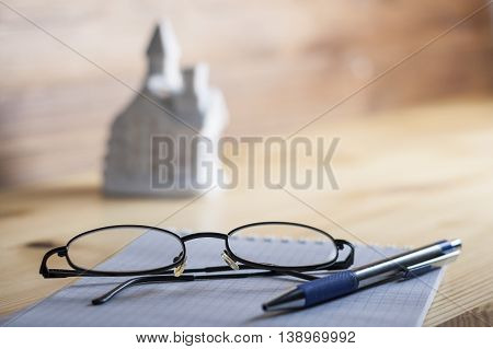 Notepad In The Box With A Pen And Glasses On A Wooden Table.