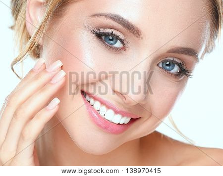 Young woman touching her face isolated on white background .