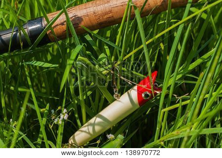 Close up section of spinning and tackle in greeen grass, concept of a rural getaway and fishing