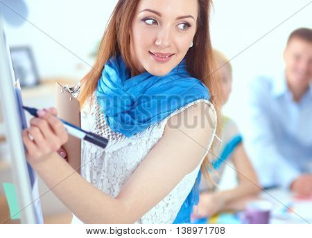 Young woman drawing on wihteboard with white copyspace.