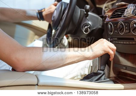 A man driving a car increases the transmission. Details.