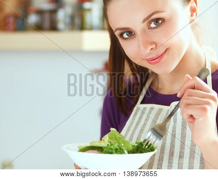 Young woman eating fresh salad in modern kitchen .