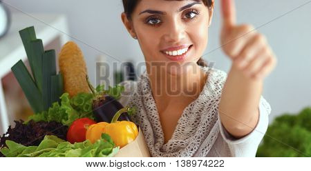Young woman holding grocery shopping bag with vegetables Standing in the kitchen and showing ok.