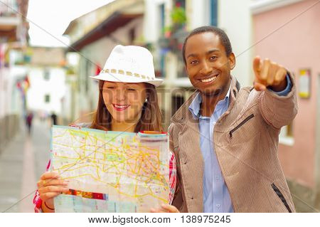 Interracial happy couple wearing casual clothes in urban envrionment, interacting and looking at map.