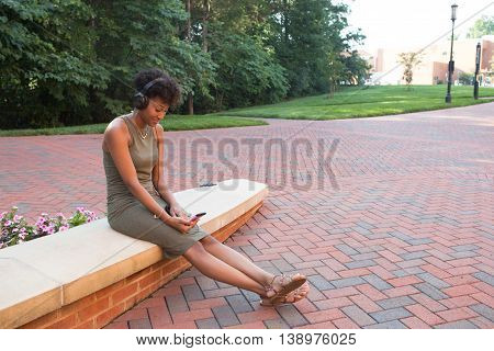 A young african american college student with a cell phone on campus