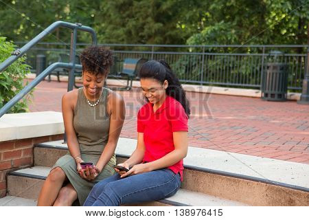 Young african american college students on campus looking at a cell phone