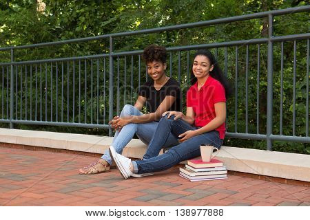 2 african american college students sitting together with their books and coffee