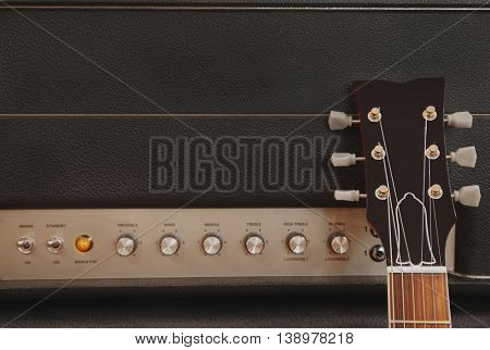 Guitar leaning up against an amplifier on stage during a concert - gritty vintage filtered background image